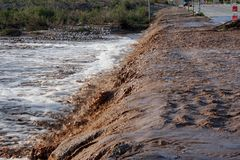 Road Washout. Flood waters crossing the road in the desert wash after the rain Royalty Free Stock Photography