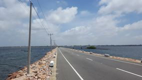 Road with water on either side. Long road through the sea Stock Photos