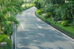 Road way among green bush and trees at countryside. Selective focus Royalty Free Stock Images