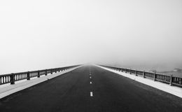 Road, way like arrow, direction to future in fog. Asphalt road on big bridge cross the lake in fog at morning, the way like arrow, direction to white future Royalty Free Stock Photo
