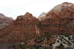 Road Weaving Through Red Zion Canyon. A deep red earth winding its way through the rugged Zion National Park. Amazing mountain structures with small green shrubs Royalty Free Stock Photo