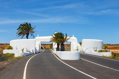 Road with white entry gate and palm trees. Lanzarote Spain royalty free stock image