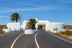 Road with white gate and palm trees, Lanzarote. Road with white entry gate and palm trees, Lanzarote Spain royalty free stock images