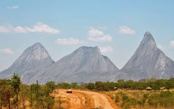 Road through the wilderness. A bush road in Africa, Mozambique with a view of inselberg mountains Stock Images