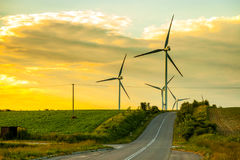 Road and Wind Power. A road through the wind power at sunset stock photos