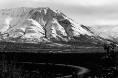 Road Winding Through Alaskan Valley With Snowy Mountains Black and White. A beautiful road winding through valley tundra landscape under a magestic snowcapped Stock Photo