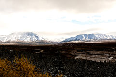 Road Winding Through Alaskan Valley With Snowy Mountains. A road winding its way through Alaskan valley tundra with two beautiful snowcapped mountains in the Stock Photos