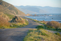 Road winding along the coast into the distance Stock Photos