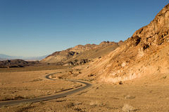 Road Winding Through Death Valley Mountains. A narrow road winding through the desert under a small mountain range in Death Valley National Park Stock Image