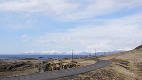 Road winding in the east fjords of Iceland. Road winding in the east fjörds of Iceland with a view on the glacier mountain range royalty free stock photos