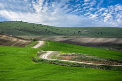 Road winding in green landscape under blue sky with white fluffy. Clouds Stock Photo