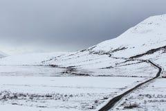 A Road Winding Through Snowy Terrain Stock Photo