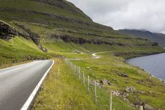 A road winds beneath the mountains and above the fjords Stock Photo