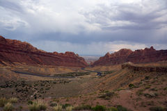 Road winds through Spotted Wolf Canyon with dramatic clouds in s Royalty Free Stock Images