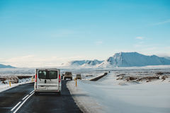 On the road in winter, with a cars driving on highway in Iceland Stock Photo