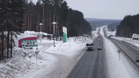 The road in the winter. Cars driving on the road. Snow-covered road near the gas station. Cars go stock video