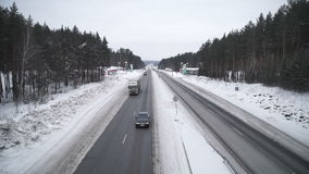 The road in the winter. Cars driving on the road. Snow-covered road near the gas station. Cars go stock video footage