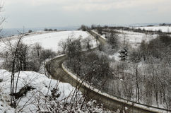 Road in winter with curves seen from distance Royalty Free Stock Photography