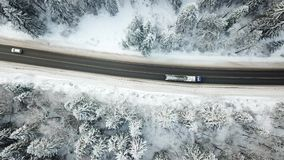 Road in winter forest. Aerial view. Passing cars, trucks. Road through the winter forest. Aerial view landscape. Passing cars, trucks stock footage