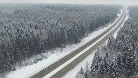 Road in the winter forest with driving cars. Aerial view. Vanishing point perspective. stock video footage