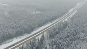 Road in the winter forest with driving cars. Aerial view. Vanishing point perspective. stock footage