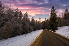 Road through winter forest at down. Road through winter forest at dusk. lovely transportation scenery in mountains with snowy hills Royalty Free Stock Photography