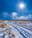 Road in a winter snowbound plain Royalty Free Stock Photo