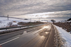Road in winter with sun at sunset Stock Images