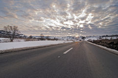 Road in winter with sun at sunset Royalty Free Stock Photo
