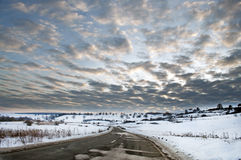 Road in winter with sun at sunset Stock Photos