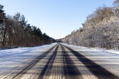 Road in winter. Wide asphalt road in the winter season. Ruts from cars on the roadway Stock Photos
