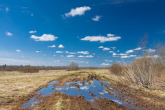 Road With Big Puddle On The Field On Countryside And Blue Sky Reflection In Puddle Royalty Free Stock Image