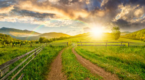 Road and wooden fence on hillside at sunset Stock Image