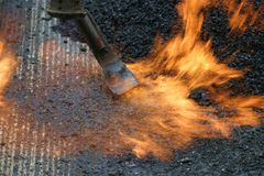Road work. Worker preparing a road for a new tar layer by using a gas burner royalty free stock photo