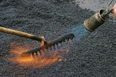 Road work. Workers preparing a road for a new tar layer by using a gas burner and rake stock photo