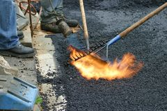 Road work. Workers preparing a road for a new tar layer by using a gas burner and rake stock photos