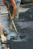 Road work. Worker preparing a road for a new tar layer royalty free stock image