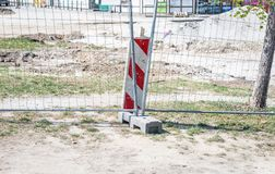 Road work ahead construction site barrier with metal protective fence on the urban street reparation in the city.  stock photography
