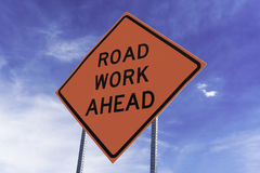 Road Work Ahead Sign. Orange Road Work Ahead sign against blue sky and white cloud background Stock Photo