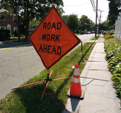 Road Work Ahead Sign with Orange Reflective Traffic Safety Cone. A large, diamond-shaped `Road Work Ahead` sign advises motorists of the utility work taking Royalty Free Stock Image