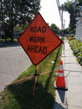 Road Work Ahead Sign with Orange Reflective Traffic Safety Cone. A large, diamond-shaped `Road Work Ahead` sign advises motorists of the utility work taking Royalty Free Stock Photo