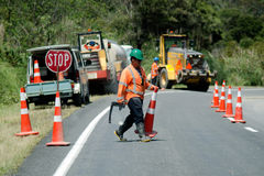 Road work. CABLE BAY, NZ - DEC 12:Road worker slows traffic with stop sign on Dec 12 2013.The Road Maintenance crew has the responsibility for the day-to-day Royalty Free Stock Images
