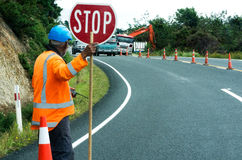 Road work. KAITAIA, NZ - NOV 05:Road worker slows traffic with stop sign on Nov 05 2013.The Road Maintenance crew has the responsibility for the day-to-day Stock Photo