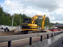 Road work in the motorway or highway. Mechanical digger Royalty Free Stock Photo