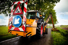 Road work in progress. Mowing with machine grass along roadside Stock Photos