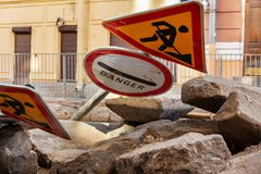 Road work sign on the stones. Symbol of caution. The yellow triangle safety sign warns you of road works. Fallen road signs on repair work in the streets of a royalty free stock photography