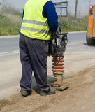 Road worker. Worker press the ground with machine Royalty Free Stock Photos