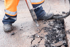 Road worker breaking street asphalt with jackhammer Royalty Free Stock Photography
