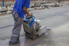 Road worker cutting asphalt road 3 Royalty Free Stock Image