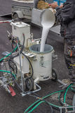 Road worker filling paint machine with paint. For marking new road lines Stock Images